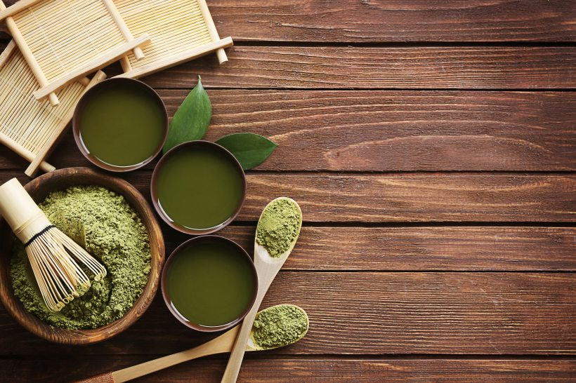 Wooden table with matcha green tea powder, matcha green tea, bamboo whisk and other tools of the Japanese Tea ceremony